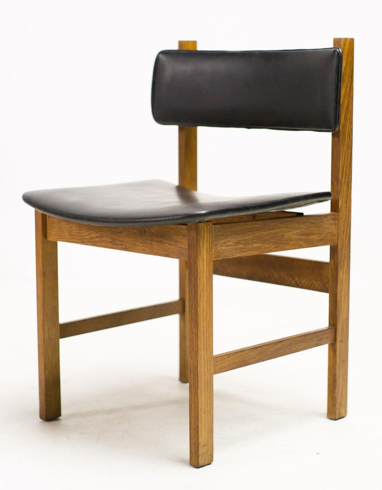 Scandinavian modern dining chairs in teak with a seat and back upholstered in black Naugahyde. All original condition, marked with stamp on the bottom.