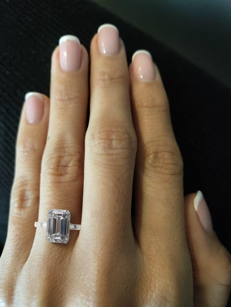Amazing emerald cut diamond ring the main stone is an exquisite 5.50 carat emerald cut diamond with J color and VS1 clarity plus triple excellent cut without fluorescence.  the side diamonds are tapered baguette and very pure   mounted in solid 950