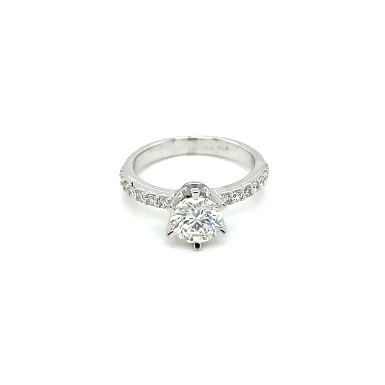18k Gold Engagement ring features 1 Round Brilliant Cut Diamond graded G color and VS2 clarity, weighing 1 ct. HRD Antwerp and adorned by 14 smaller round brilliant cut diamonds, having a total weight of 0.60 ct  The diamond has the certificate