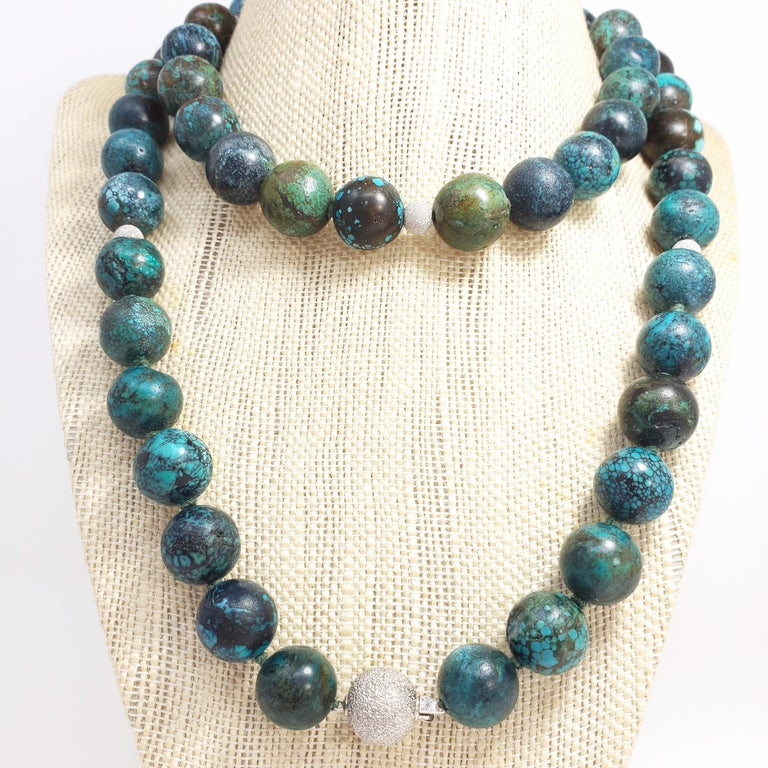 An exquisite Hubei turquoise bead necklace. This 34-inch, knotted string necklace features a series of round, 14mm, turquoise beads with exotic-looking matrix patterns. The polished gemstones are a rich, unique, and vibrant color, and are accented