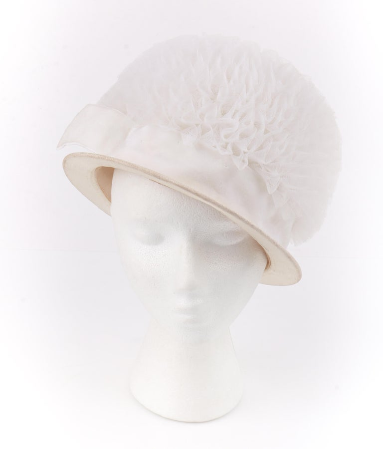 HUBERT DE GIVENCHY ADAPTION c.1950's Gathered Tulle Velvet Ribbon Cloche Hat  Circa: 1950's  Label(s): Hubert de Givenchy; Union label Style: Cloche Hat Color(s): Shades of white / cream Lined: No Unmarked Fabric Content: Tulle (exterior); velvet