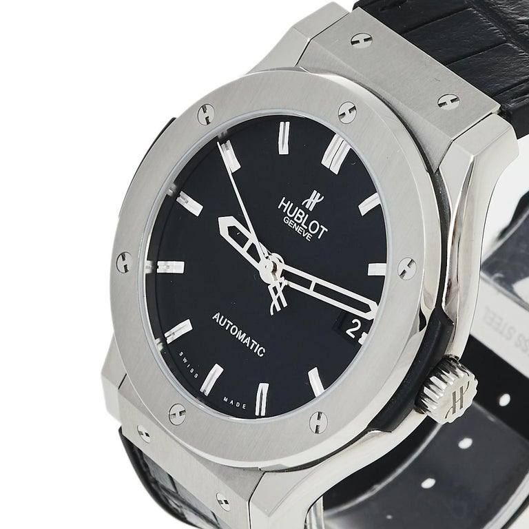 Not only is this stylish Hublot Classic Fusion wristwatch comfortable to wear, but it's also well-crafted and attractive. The titanium case with a punctuated bezel surrounding a black dial on a tonal strap looks elegantly timeless. Its impressive