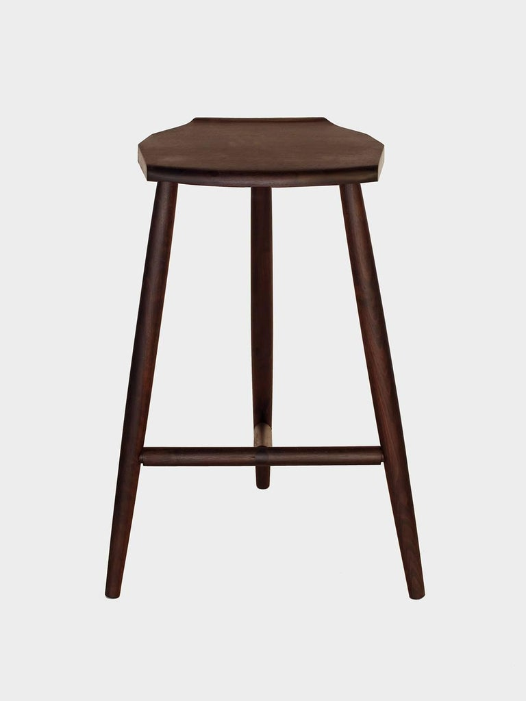 New York Heartwoods' ebonized black walnut solid wood counter height stool is influenced by Mid-century and Shaker design, features three hand-turned legs, a shaped faceted seat, and wedged tenons.  Designed for comfort and stability, each stool is
