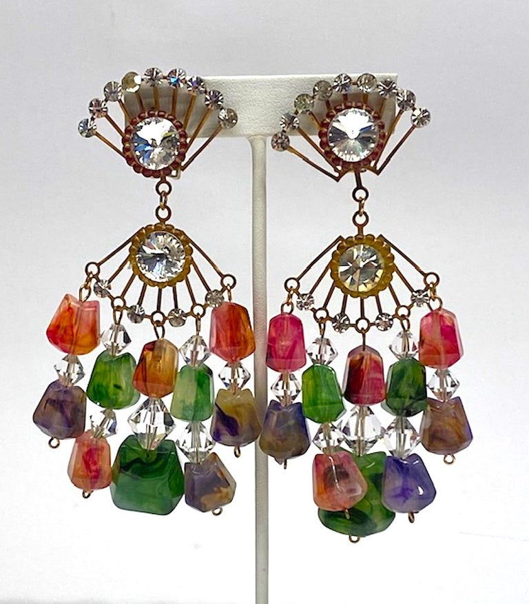 A true vintage and statement pair of chandelier earrings from the early 1970s. Each earring is comprised of two 1.5 wide by 1 inch high fan shape antique brass patina findings. Each set with small round rhinestones and one large rivoli rhinestone.