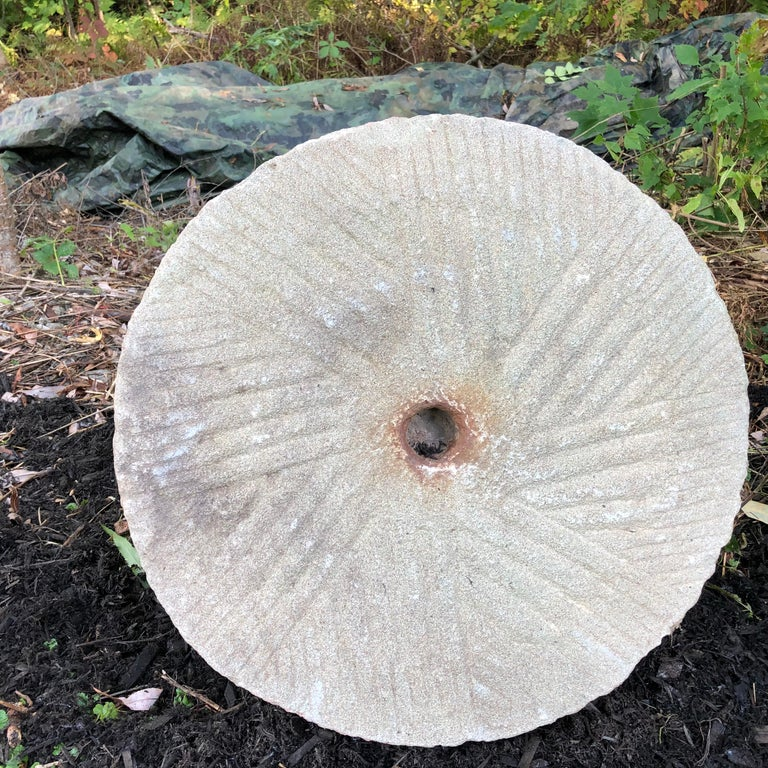 From China, comes this huge 22 inch diameter round hand-carved mill stone from the 19th century or earlier period. This was likely a grinding base stone for a large oil pressing tool and device.  Dimensions: 22 inches diameter and 5 inches thick