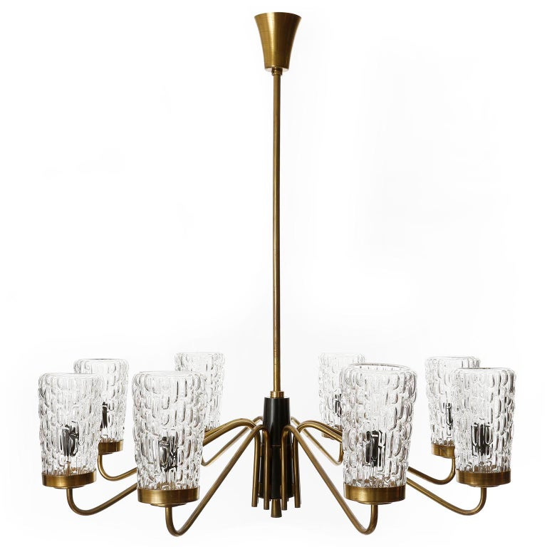 An extra large eight-arm chandelier by Rupert Nikoll, Vienna, manufacured in Mid-Century, circa 1960 (late 1950s or early 1960s).  The fixture is made of a nice mixture of materials: large textured clear glass lamp shades, patinated brass and black