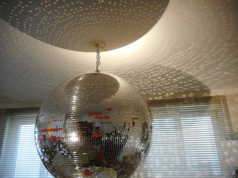 Directly from a former ballroom, extra large mirror ball covered with a multitude of little mirrored squares.