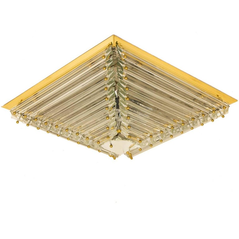 A gold-plated Venini flush mount with faceted clear crystal tubes of Murano glass. Modellated in the form of a pyramid. The flush mounts are designed and produced by Venini in Italy from the 1970s. The Murano tubes are suspended on a gold-plated