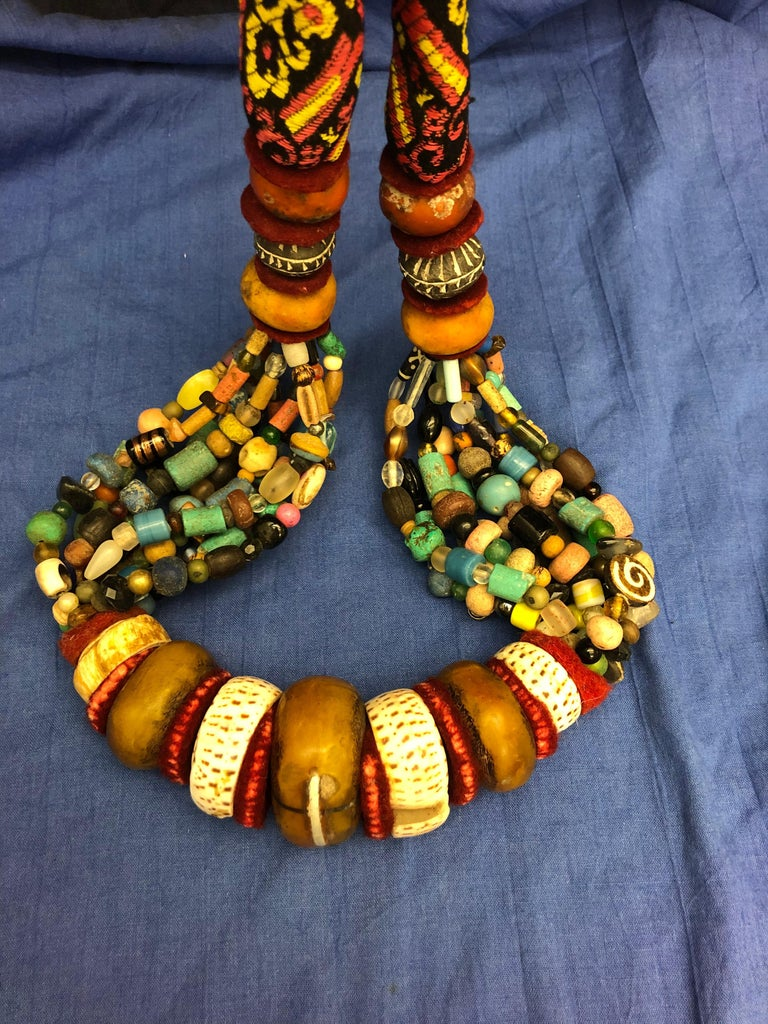 This giant handmade Berber necklace is intended to be worn during tribal wedding celebrations or to be displayed on the wall. The centre of the necklace has a very large copal bead that has been repaired with a large silver staple. Two snail shells