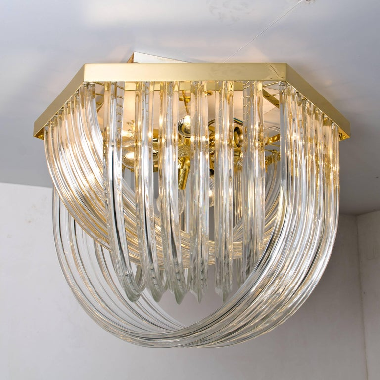 A huge and impressive Venini flush mount chandelier, curved crystal glass and gilt brass, Italy  The chandelier is made of curved crystal Murano glasses in different lengths. The flush mount has eight lights with 18 Murano crystal tubes and a