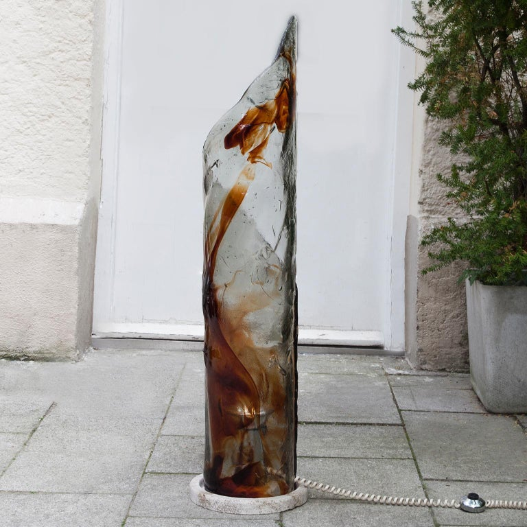 Murano glass floor lamp sculpture attributed to Carlo Nason for AV Mazzega, Italy, 1970s. Beautiful travertine base with heavy amber and clear colored Murano glass. Carlo Nason is probably one of the most important Murano glass makers. 1 sockets