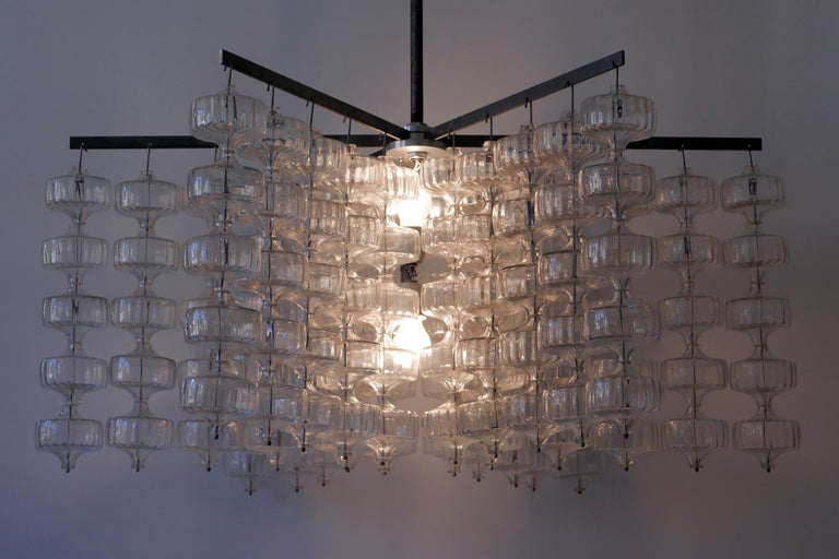 Huge, spectacular Mid-Century Modern chandelier or pendant lamp by Aloys Ferdinand Gangkofner, 1968, Germany.  Executed in hand blown glass, this exceptional chandelier comes with 150 glass elements which hang from 6 steel arms in five rows. It