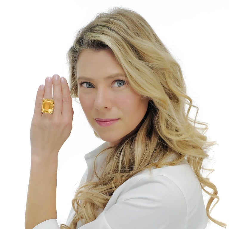 Circa 1970, 18k.   This spectacular ring features a 65 carat citrine in a visionary, modernist setting. Stripped down to the essentials, form and function become one. The vivid, yellow gold, emerald cut citrine is the perfect choice in shape and hue