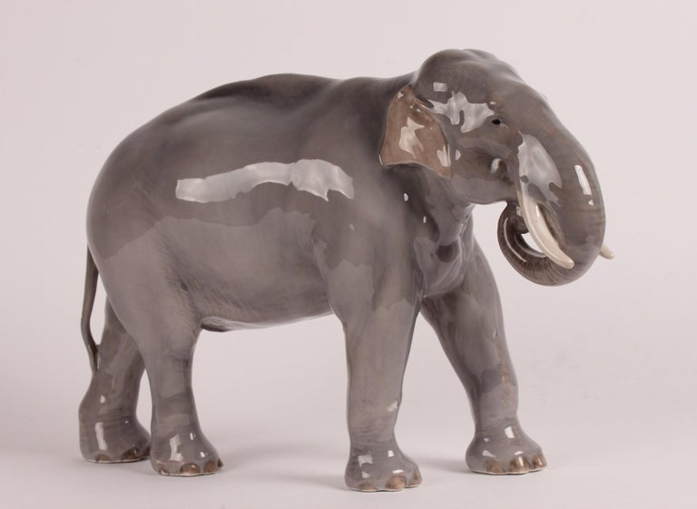 Huge Danish porcelain figure of an elephant model 447 designed by Theodor Madsen and manufactured by Royal Copenhagen.  The figure is decorated with glossy glaze in grey, brown and creamy white colors  Stamped with the three waves of Royal