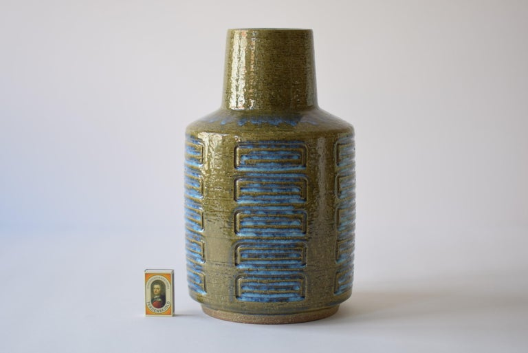 This huge budded vase was designed by Per Linnemann-Schmidt for Palshus and was produced in Denmark during the 1960s or early 1970s. It has a shiny glaze in moss green with blue in the incised stripes and on the shoulder. The vase is made with the