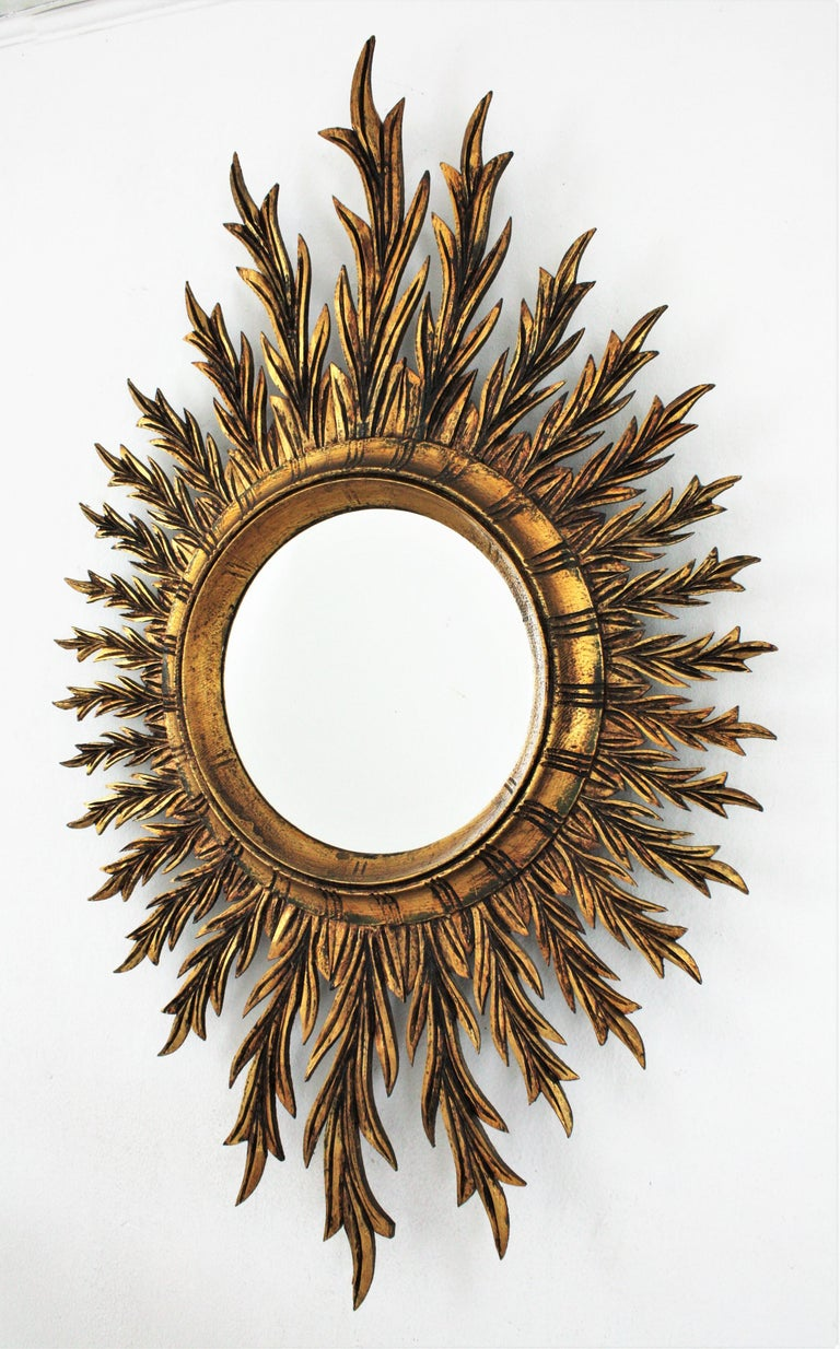 An amazing finely carved giltwood oval shaped starburst /sunburst mirror with gold leaf finish in the style of Hollywood Regency, Spain, 1950s-1960s. This mirror has a richly carved frame with rays full of movement in different sizes. It is covered