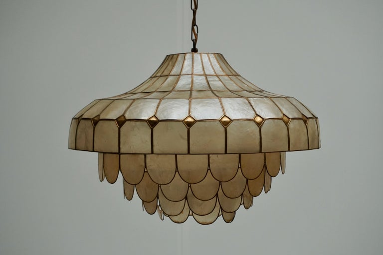 Gorgeous pendant lamp with countless mother-of-pearl or nacre pieces and brass details forming a hugh magic hat.  Stunning piece, checked and cleaned.