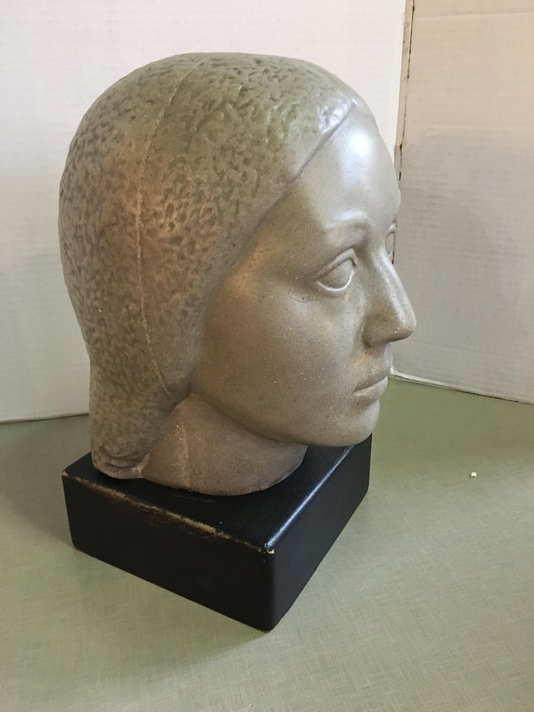 A limestone head of a woman sculpture on a base by Humbert Albrizio.