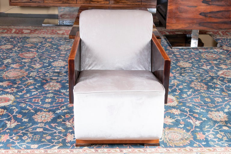 Armchairs are made out of walnut wood and re-upholstered in a light velvety fabric. Arms of the chair is made out of solid piece of wood. On the side beautiful woodgrain is visible. Chair rests on the 4 square wooden legs.  Back of the chair is
