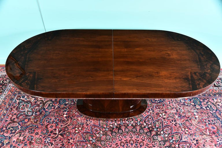 Hungarian dining room table in walnut, Art Deco period Great Art Deco table made out of fine walnut wood. It has oval tabletop with chrome trimming on the edge. Tabletop has one insert. Top is supported by the oval elongated leg and a base. Base