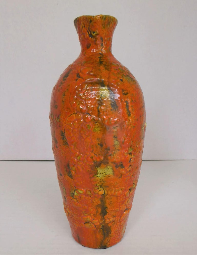 This lovely Hungarian lava glaze handled Ewer in bright orange dates from the late 60s to early 1970s. The heavy tomato orange glazed has been fired on a yellow background which peeks in parts under the lava glaze and has been applied over the dark