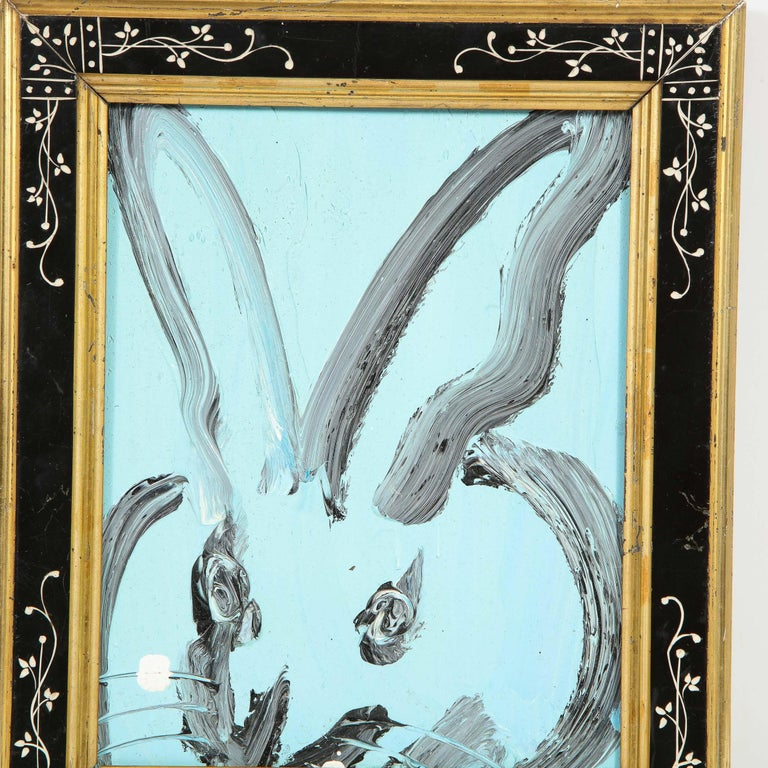 This whimsical and sophisticated painting was realized by the esteemed contemporary painter, Hunt Slonem in 2015. It presents a stylized bunny rabbit, rendered with loose and expressive brush strokes in black paint against a vibrant sky blue