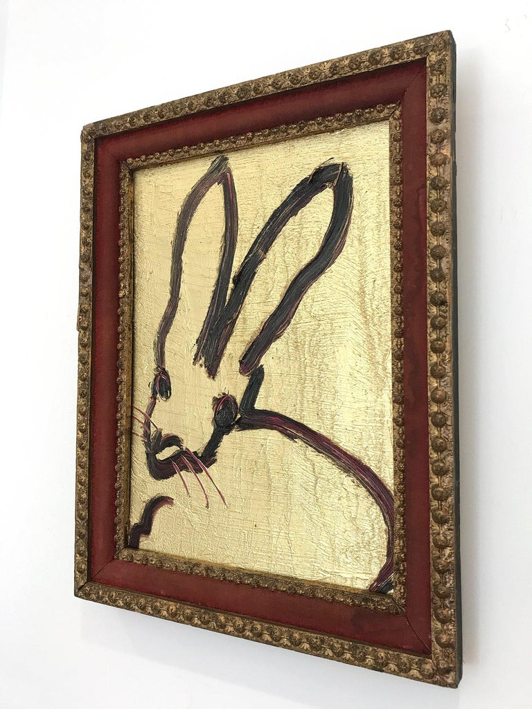 A wonderful composition of one of Slonem's most iconic subjects, Bunnies. This piece depicts a gestural figure of a black bunny on a gold background and Ruby accents with thick use of oil paint. It is housed in a wonderful antique 19th Century
