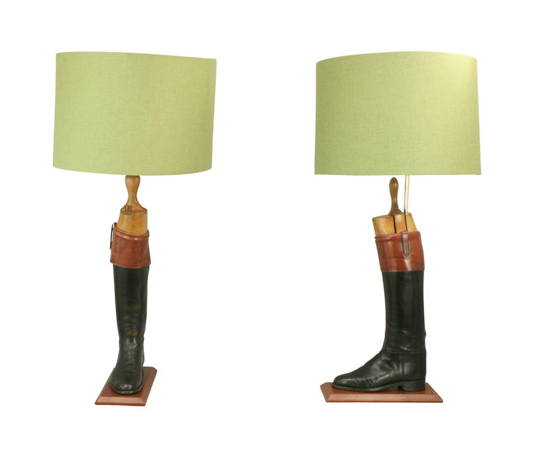 Vintage pair of black hunting or riding boot lamps. A pair of English leather hunt or top boots with the original beech wood trees. The black hunting boots with 'Mahogany' tops (tan cuff) have been sympathetically converted into a pair of