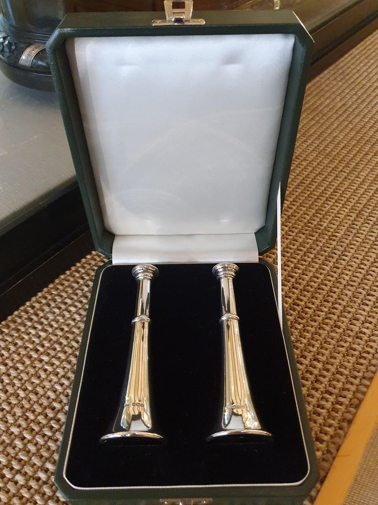 Walker & Hall, Sheffield  A pair of sterling silver salt and pepper pots in the form of hunting horns. Bearing hallmarks for Sheffield 1934, the pots are complete with a green calfskin presentation case.   Measure: Height of each pot: 6 inches