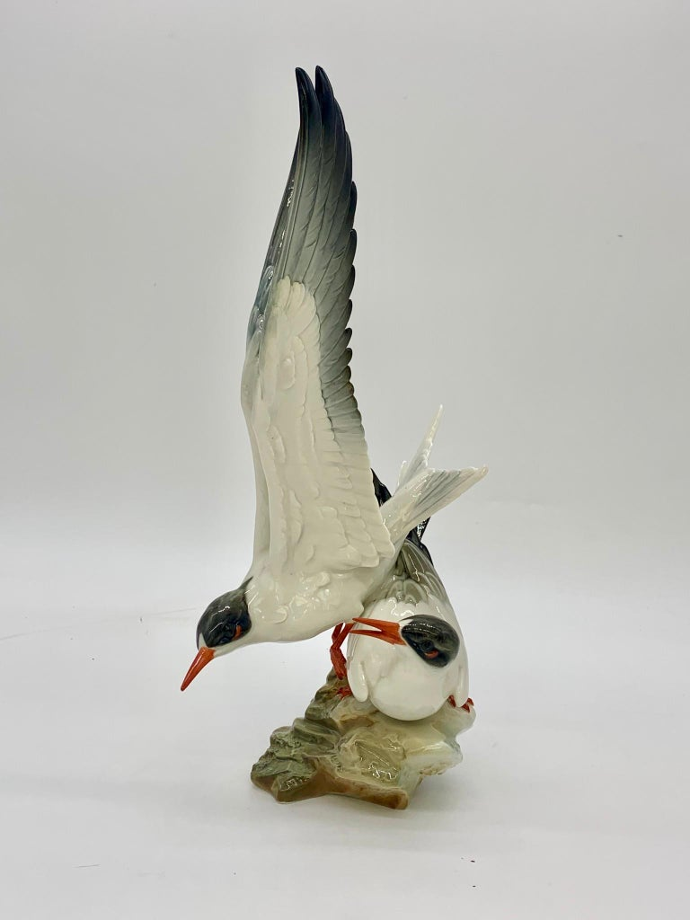 """Two beautiful birds with grey and white feathers and orange beaks. One in mid-flight by German porcelain manufacture Hutschenreuther.  Mark of hutschenreuther """"kunstabteilung (artwork)."""