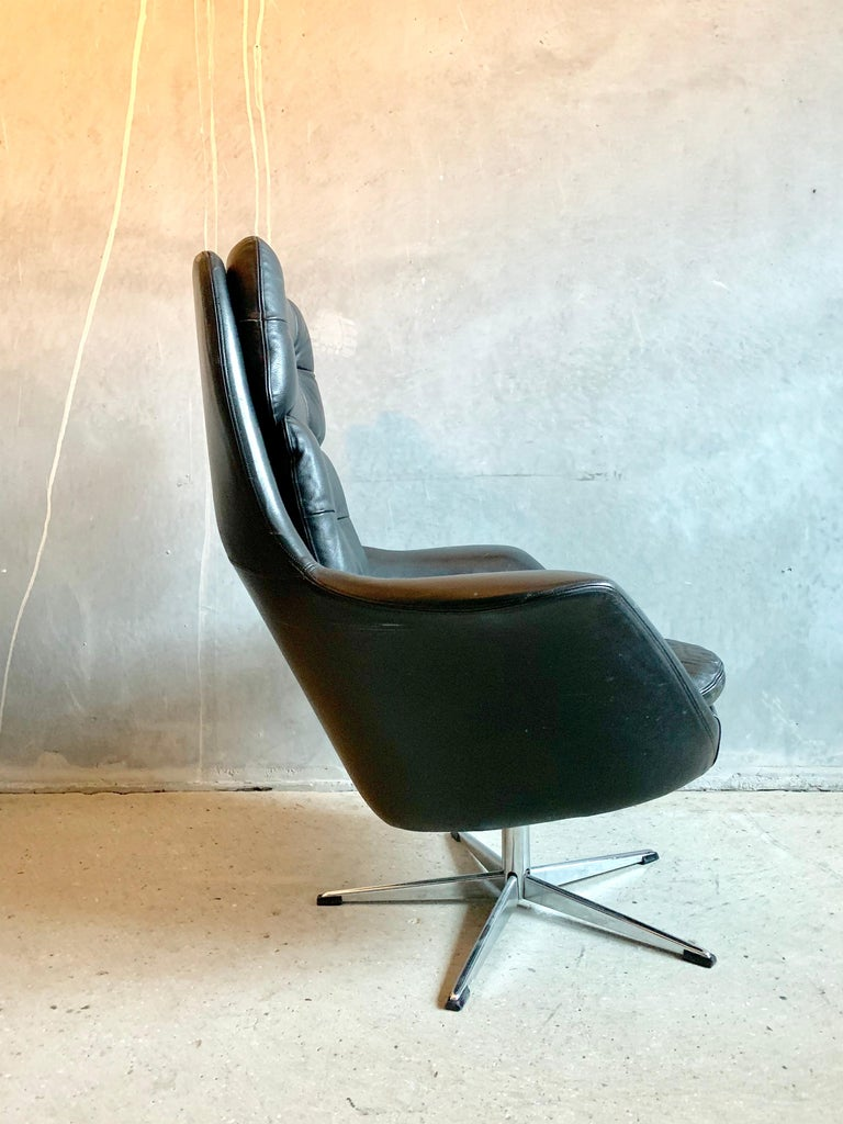 Swivel armchair designed by H.W Klein for Bramin, Denmark. Upholstered with button tufted black leather, frame of stainless steel with matching foot stool.