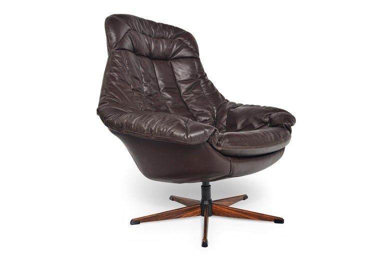 This Space Age swivel chair was designed by H.W. Klein for Bramin in the 1960s. With a sleek, organic form, this chocolate brown leather lounge chair is upholstered on all sides and holds a single cushion which drapes over the frame. The swivel base