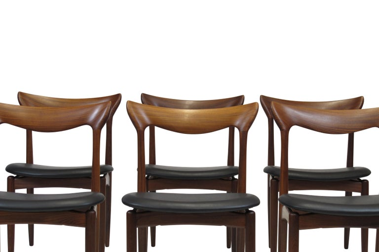 Exquisite set of six HW Klein teak dining chairs (circa 1960) with hand sculpted backrest, tapered leg, and floating seats newly upholstered in black leather. The chairs have been fully restored in a natural oil finish. Immaculate condition.