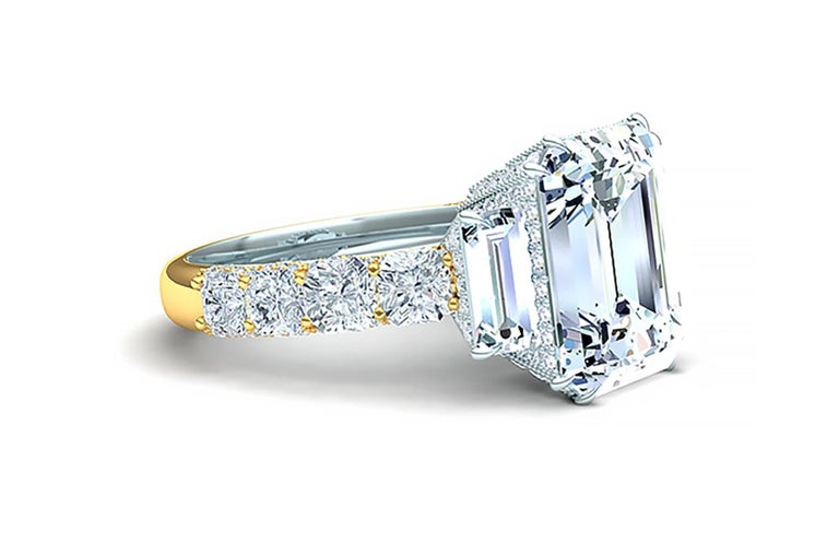 This modern twist on a classic engagement ring design gives the one wearing it a bespoke look that is surely know to be custom when seen.  The center diamond is emerald cut and has a color and clarity of I-VS2 and is GIA certified.  The center stone