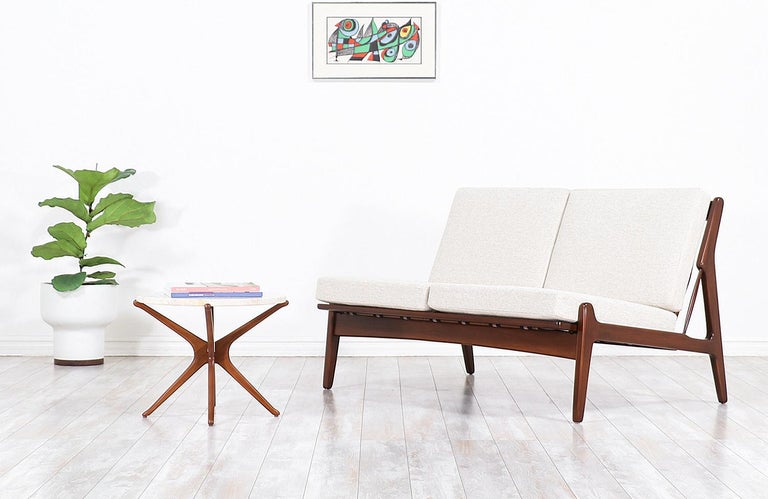 Elegant modern love seat designed by Danish architect and furniture designer Ib-Kofod Larsen for Selig in Denmark, circa 1960s. This beautiful and compact sofa features a solid sculpted walnut-stained Beechwood frame with vertical slats at the back