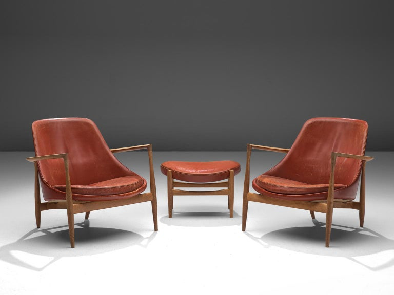 Ib Kofod-Larsen, two lounge chairs with ottoman, model U-56 'Elizabeth', oak and red leather, Denmark, 1956.  These are two of Kofod-Larsen highest-quality armchairs, with an oak frame and beautiful details in the design. The leather holds beautiful