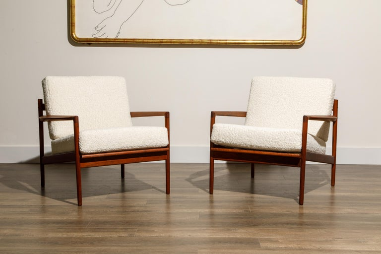 Newly reupholstered in gorgeous white bouclé fabric, this pair of lounge chairs by IB Kofod-Larsen for Selig, circa early 1960s, feature beautiful teak frames with on-trend slatted backs. Incredible designer details abound, from the sculpted arms,