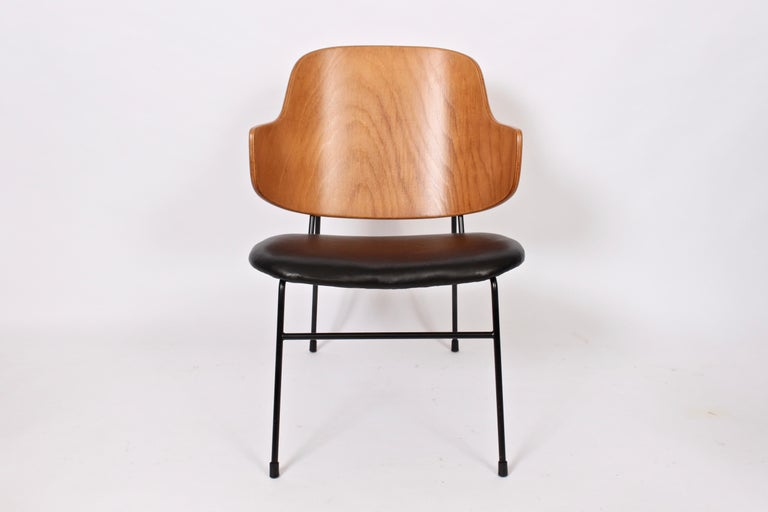 Classic Danish modern Kofod-Larsen penguin chair. Featuring a sturdy black wrought Iron framework with capped feet, slightly slanted and newly upholstered black leather seat with comfortable angled bentwood seat back. (Seat height 13