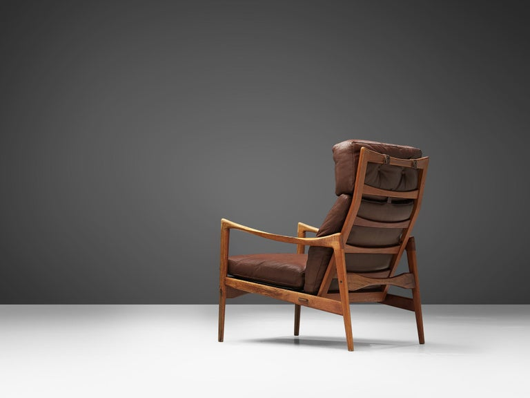 High back chair, in teak and leather, by Ib Kofod-Larsen for OPE Möbler, Sweden, circa 1963.  Elegant high back armchair in teak and brown leather upholstery. The frame shows the great skills of Ib Kofod-Larsen. Elegant lines and curves and a