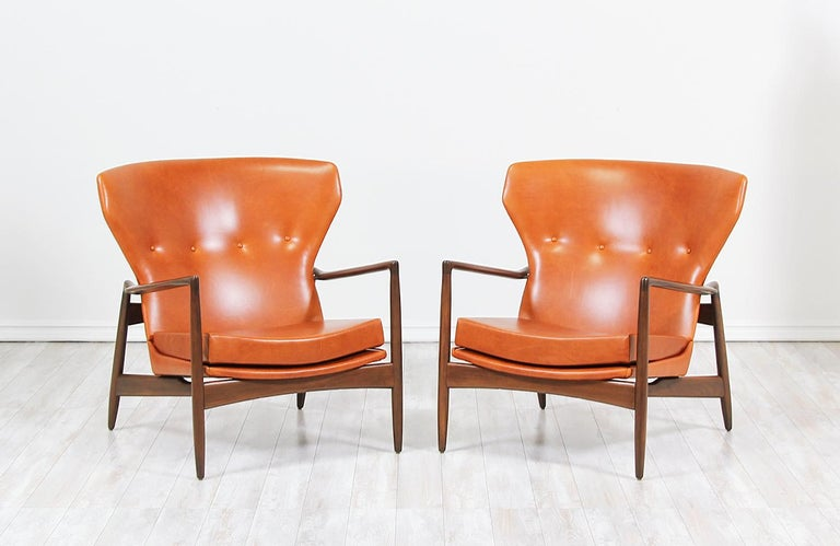 Pair of stylish lounge chairs designed by Ib Kofod-Larsen for Selig in Denmark, circa 1960s. These bold wingback style chairs feature a sculptural walnut-stained beechwood frame that holds the seat with a high-back and lower armrests emphasizing its
