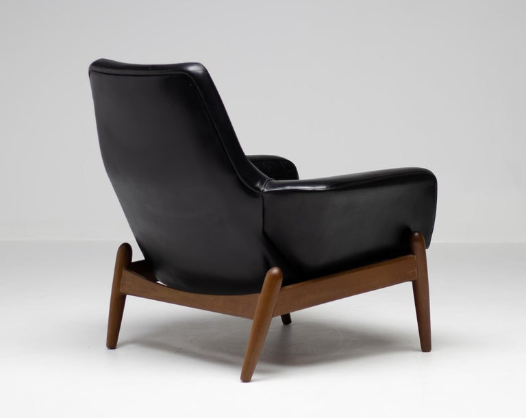 Very comfortable lounge chair designed by Ib Kofod Larsen in teak and black leather.