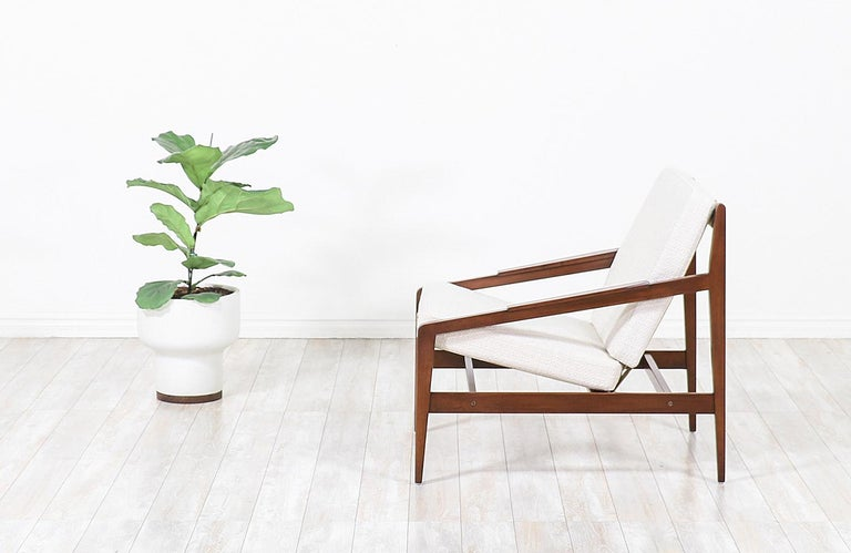 Elegant modern lounge chair designed by Ib Kofod-Larsen for Selig in Denmark, circa 1960s. This beautiful ergonomic lounge chair features a sturdy walnut-stained beech-wood frame with an angled seat and back that is held in place by new Pirelli