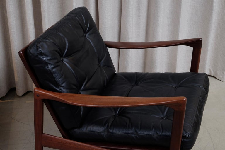 Afromosia and black leather cushions. Excellent vintage condition. Produced by OPE, 1960s.  Please note: set of 4 available.  Listed price is for one pair.