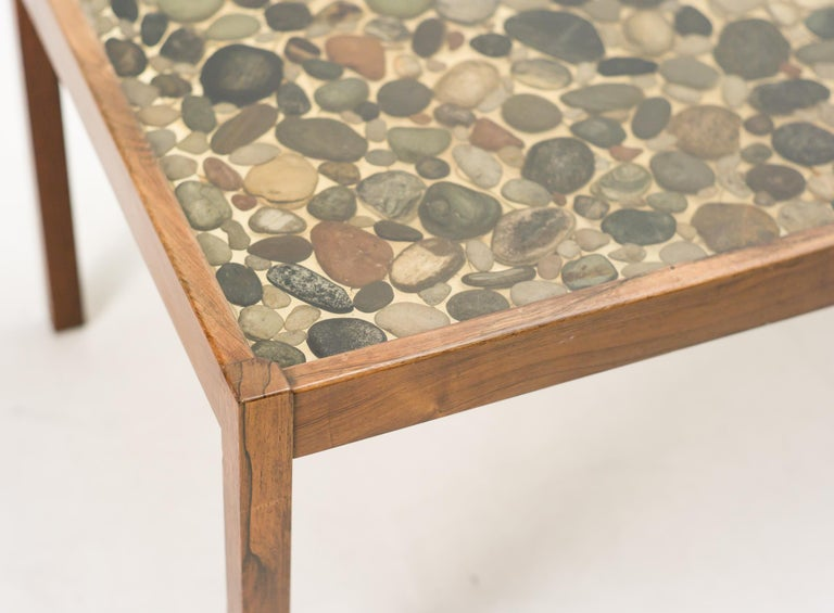 Teak coffee table designed by Ib Kofod-Larsen for Seffle Möbelfabrik. Remarkable coffee table with a polyester top with cast in natural pebbles.