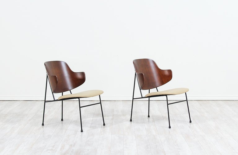 Iconic pair of 'Penguin' modern lounge chairs designed by Ib Kofod-Larsen for Selig in Denmark, circa 1960s. These timeless Danish modern chairs feature a structurally sound black iron frame that supports the newly refinished molded bentwood