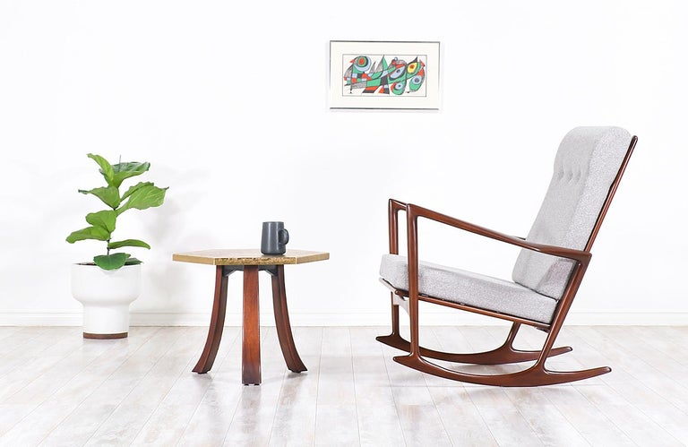 Rare modern rocking chair designed by Ib Kofod-Larsen for Selig in Denmark circa 1960s. This elegant rocking chair frame is crafted in walnut-stained beechwood with an open back and sculpted armrests creating a gorgeous modern profile. This iconic