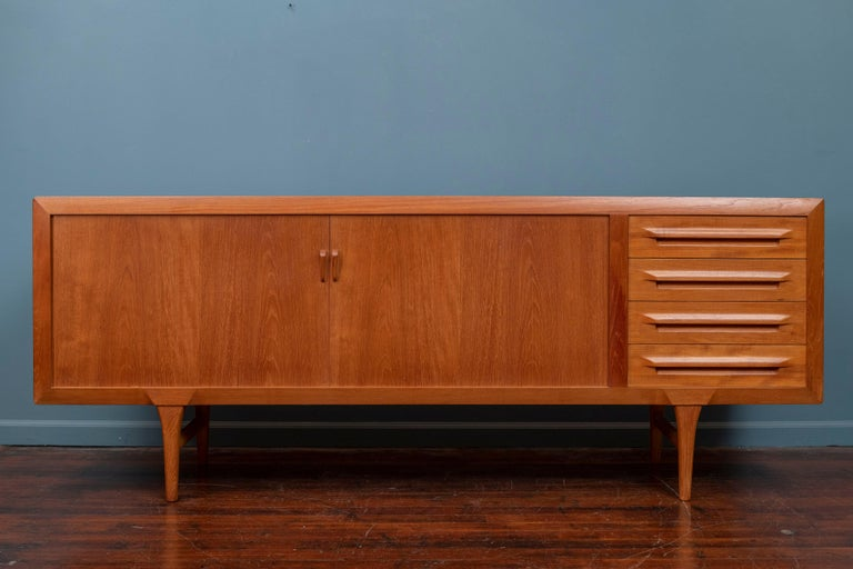 Tambour door credenza designed by Ib-Kofod Larsen for Faarup Møbelfabrik in Denmark, circa 1950s. Impeccably crafted in teak wood, this beautiful credenza shows an intricate wood grain throughout and features smoothly functioning tambour doors that
