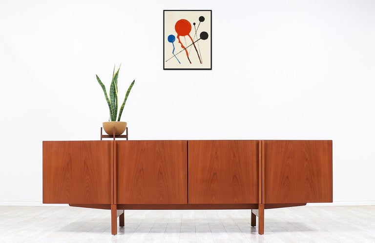Minimalist credenza designed by Ib-Kofod Larsen in collaboration with the workshop of Faarup Møbelfabrik in Denmark circa 1950s. Impeccably crafted in teak wood, this beautiful credenza shows an intricate wood grain throughout and features smoothly