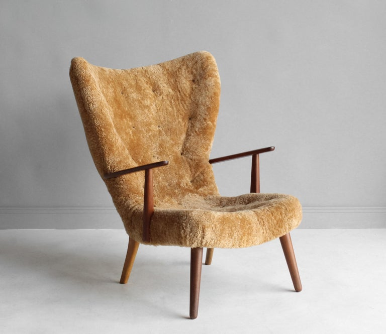 A high back lounge chair / armchair. Designed by Ib Madsen & Acton Schubell. Produced in Denmark, 1950s. Designers mixes typical mid-century aesthetics with organic form.   Teak and beech frame, upholstered in brand new authentic lambskin /