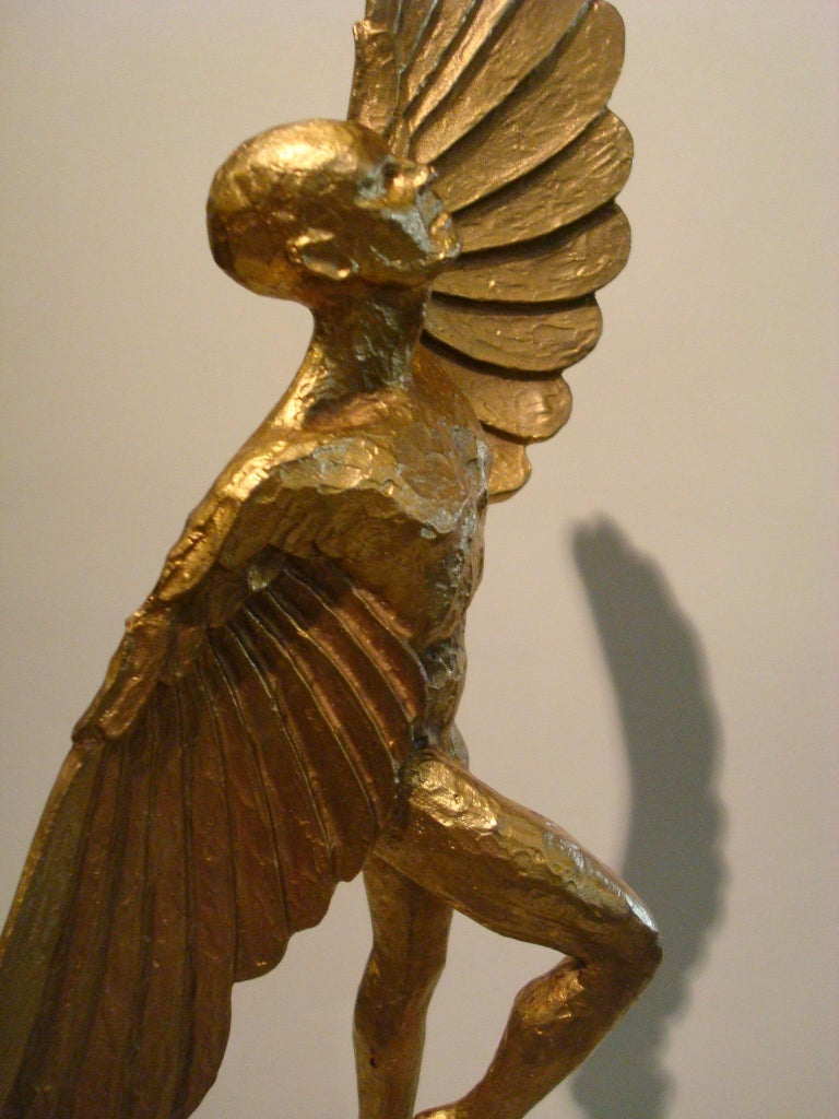 Icarus. Art Deco gilt bronze sculpture of an athletic man with stylized wings, mounted over a marble base.
